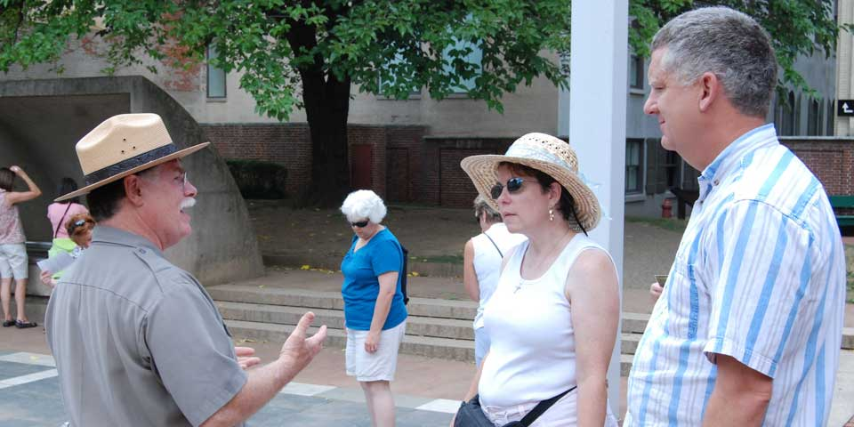 Color photo showing a male park ranger speaking to a man and a woman in the Franklin Court Courtyard.