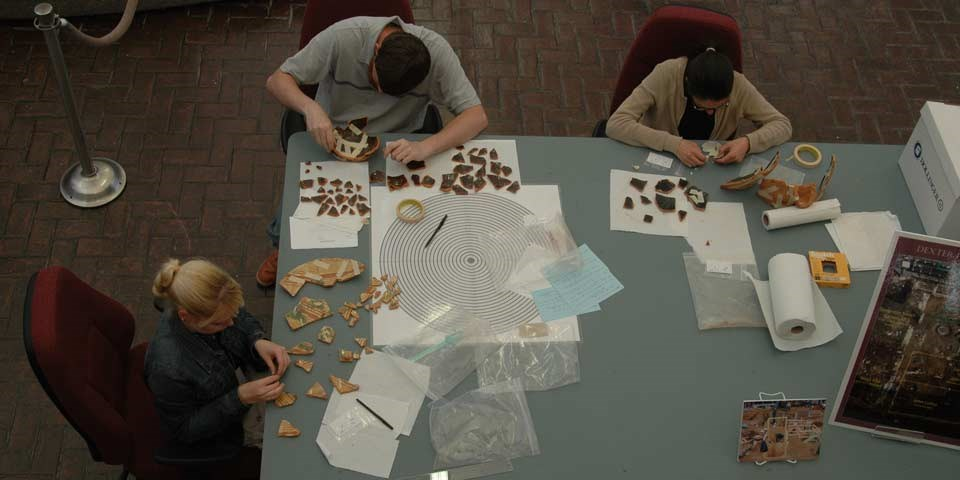 Color photo of three people seated at a table piecing together bits of pottery.