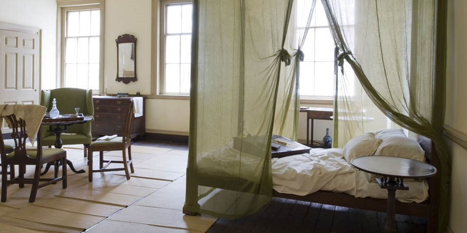 Color photo of the Bishop's bedroom with a four poster bed draped with thin gauze mosquito netting in the foreground and a table surrounded by mahogany chairs and an easy chair in the background.