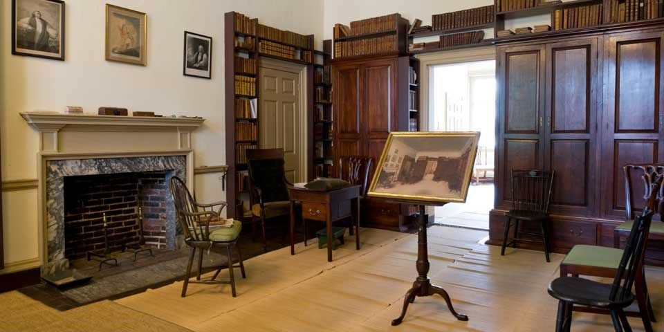 Color photo of room with bookcases along two walls, and early 19th century furnishings throughout the room.