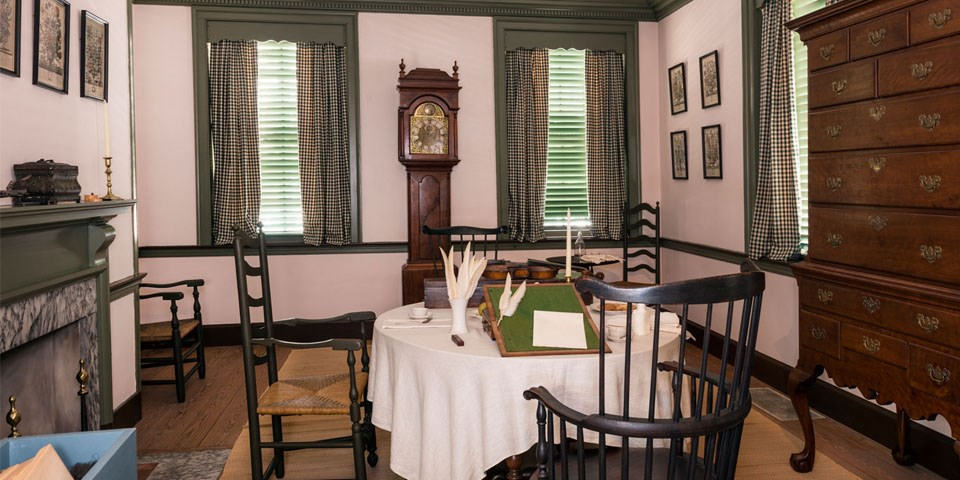Color photo of the Declaration House parlor with a Windsor chair and table, tall chest, and tall case clock.