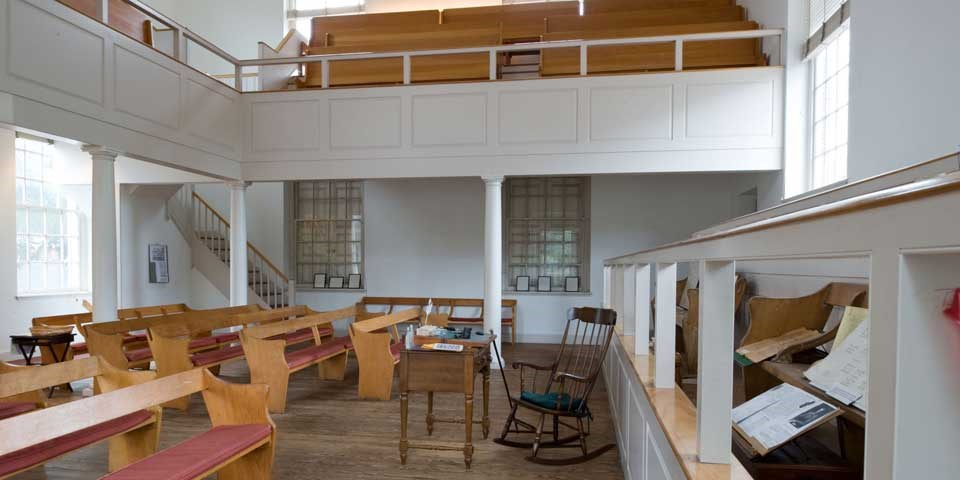 Color photo showing wooden pews facing a rocking chair in the front of the room with a balcony above.