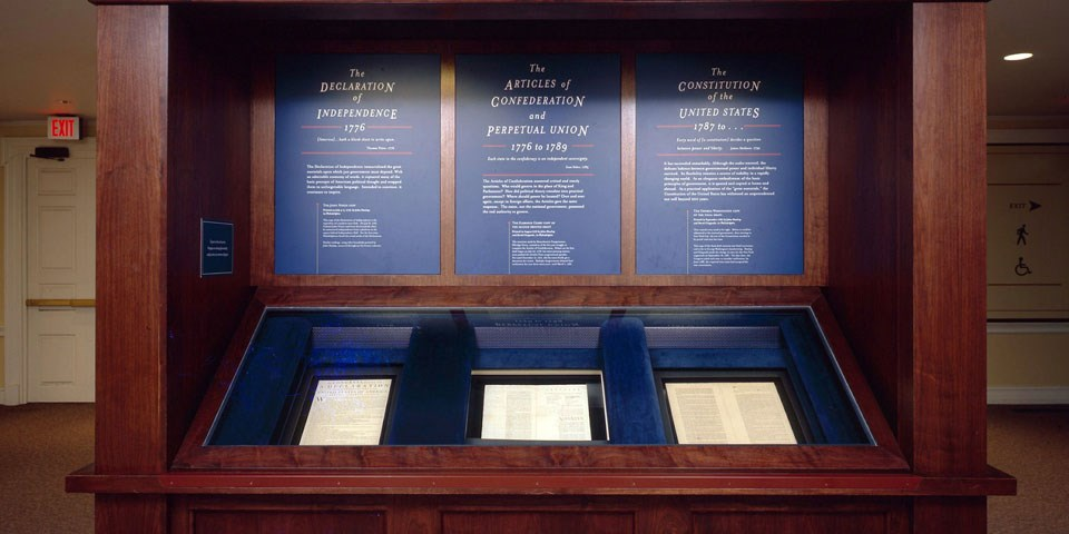 Color photo of a wooden exhibit case displaying three documents, side by side, at waist height with blue text panels above.