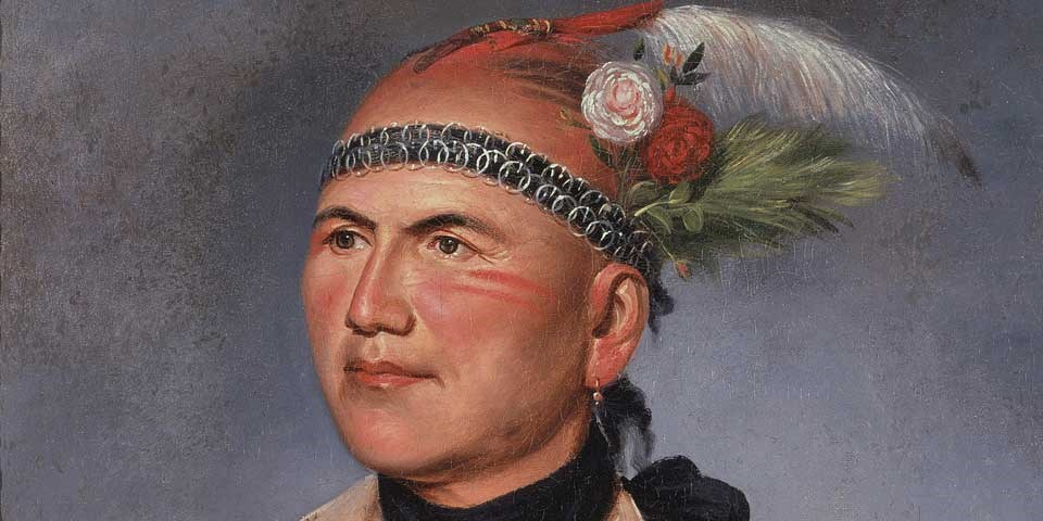 Color image of a detail of a painting of Joseph Brant/Thayendanegea, showing his face.  His black hair is in a scalp lock decorated with feathers and flowers, and he wears a black headband with silver rings.