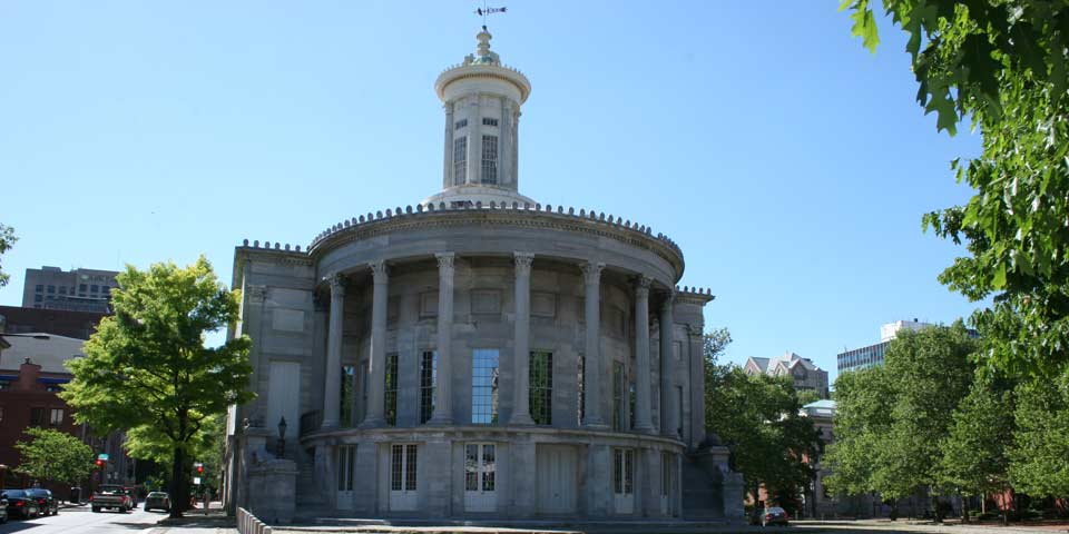Color photo showing rounded east facade of marble building with many columns.