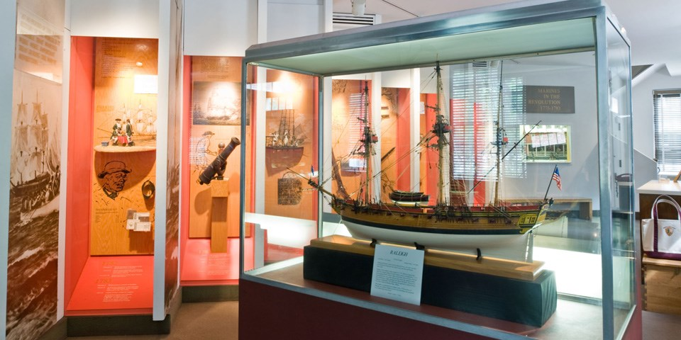 Color photo of exhibit area with ship model in case in foreground.