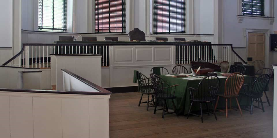 Color photo of courtroom with six chairs on dais, raised above a wooden jury box, and one table surrounded by Windsor chairs.