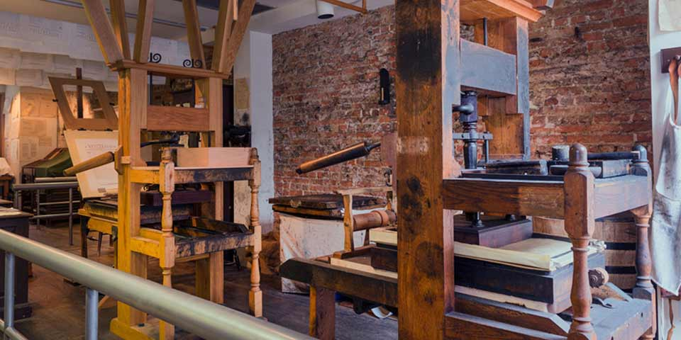 Color photo of two reproduction 18th century printing presses made mainly of wood.