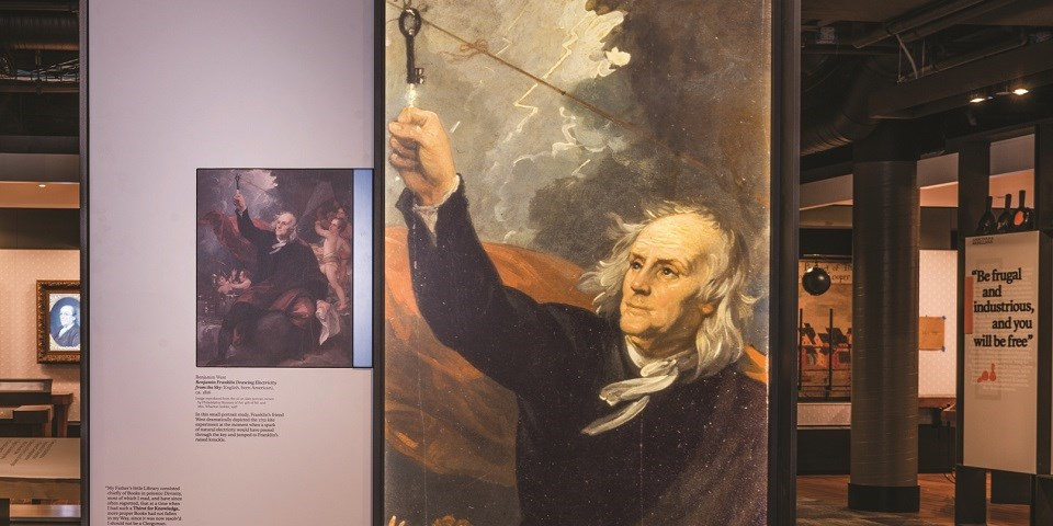 Color image of an exhibit with an image of an older Benjamin Franklin holding up his knuckle to touch a black key on a string.