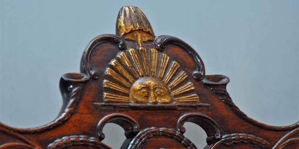 Color photo showing close up of sun, liberty pole, and liberty cap carved into crest rail.