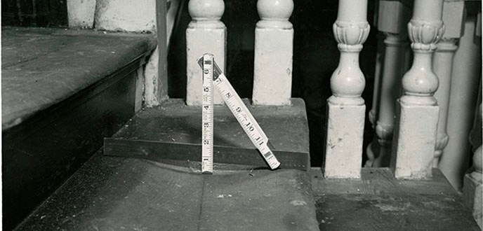 Photograph of stair tread in Independence Hall's staircase with ruler showing the degree of wear caused by visitors' feet.