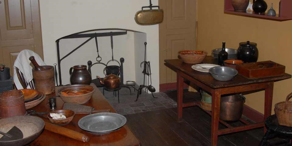 Color photo of the Todd House kitchen showing a narrow work space with wooden work tables on either side of the room and a fireplace along the back wall.  Redware bowls and pewter utensils sit on the tables and near the fireplace.