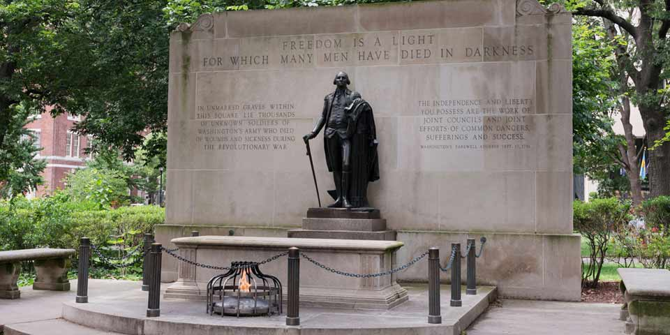 "Color photo of statue of George Washington on plinth in front of tomb and eternal flame.  Behind Washington is a wall with text reading ""Freedom is a light for which many men have died in darkness."""