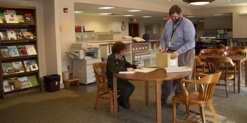 Color photo of an archivist putting a box of archival material on a table near a seated female park ranger.