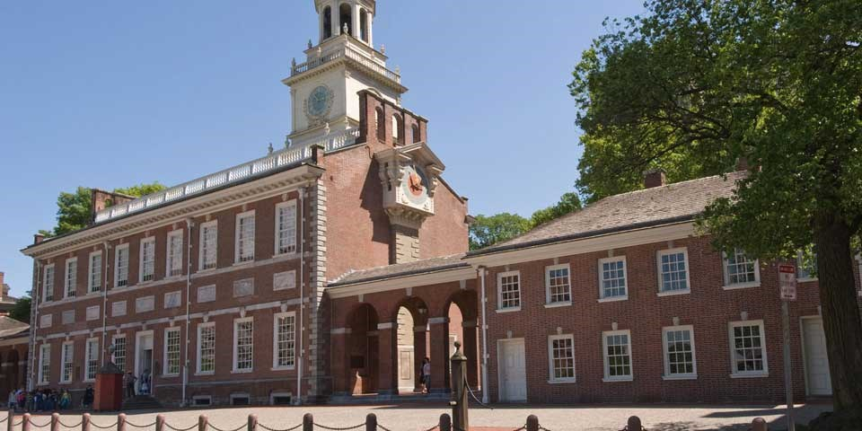 Color photo of Independence Hall and its West Wing, showing a large two story red brick building with central clock tower and adjoining smaller two story red brick building.