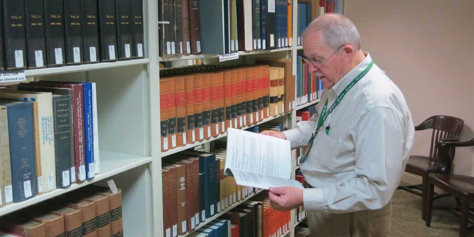 Color photo of a man standing next to a bookshelf in a library, holding a book.