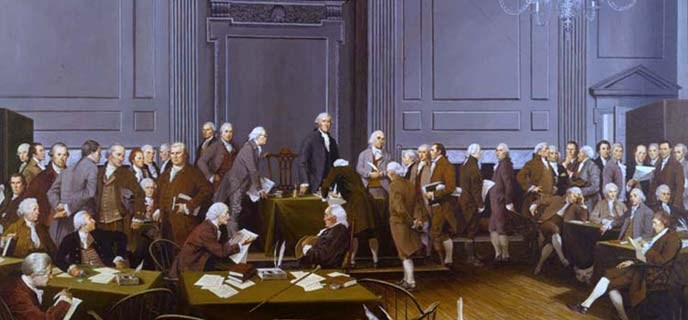 Color photo of a painting showing the signers of the U.S. Constitution in the Assembly Room.  George Washington stands at a table in the front of the room with a row of men on either side of him.  A few others sit at nearby tables.