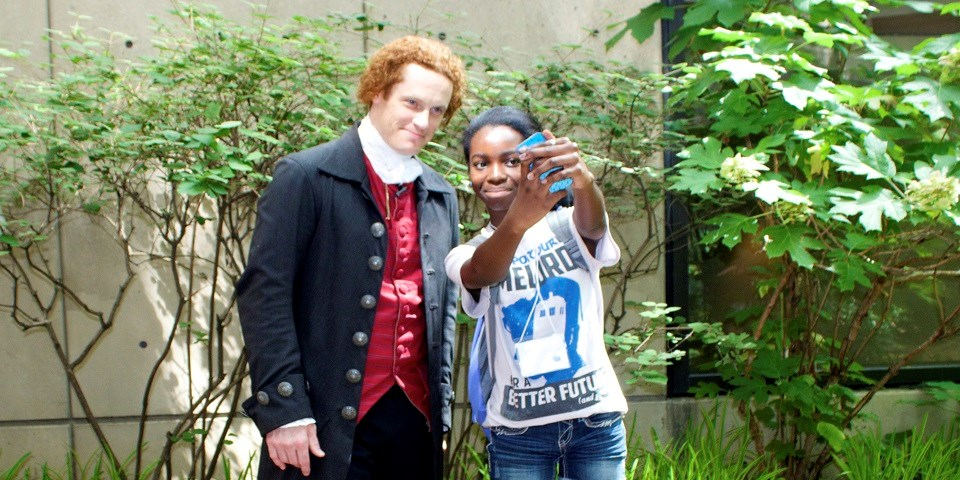 Color image of a man dressed in colonial garb posing for a selfie with and a teen girl.