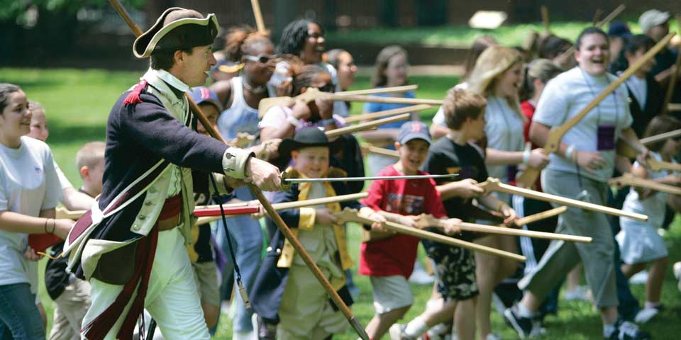 Color photo showing people of all ages running with wooden muskets while a man in colonial military uniform encourages them on.