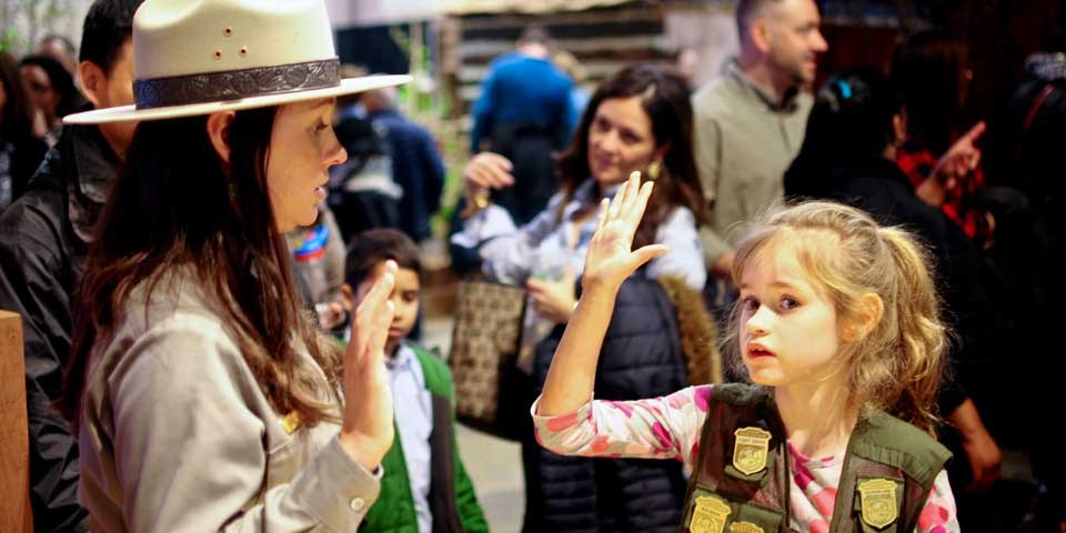 Color photo of female park ranger swearing in young girl as junior ranger.