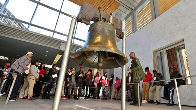Park Ranger standing at the Liberty Bell with students.