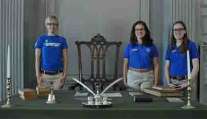 Student Conservation Association Interns, wearing blue shirts, stand next to the Rising Sun Chair. Table with green cloth is in front of them. On the table sits a replica of the inkstand used to sign the Declaration of Independence.