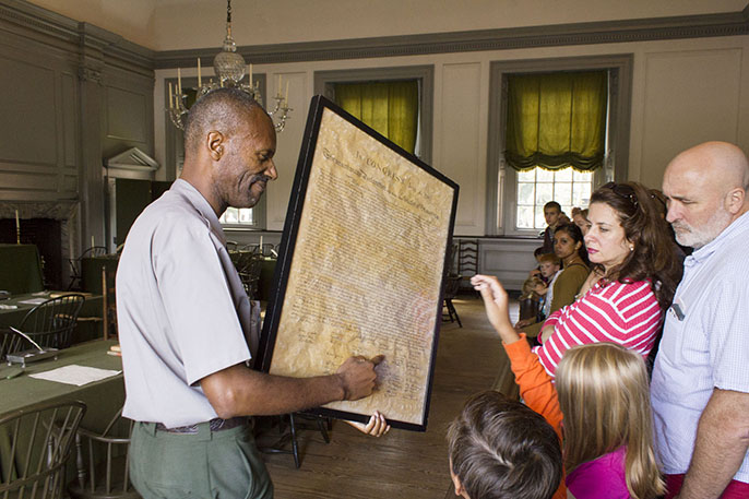 National Park Service Ranger talks to visitors while showing a copy of the Declaration of Independence.