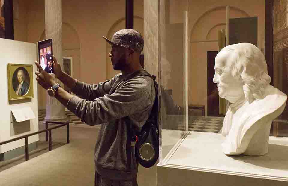 Park visitor takes a selfie with bust of Benjamin Franklin in the Portrait Gallery at the Second Bank of the United States.