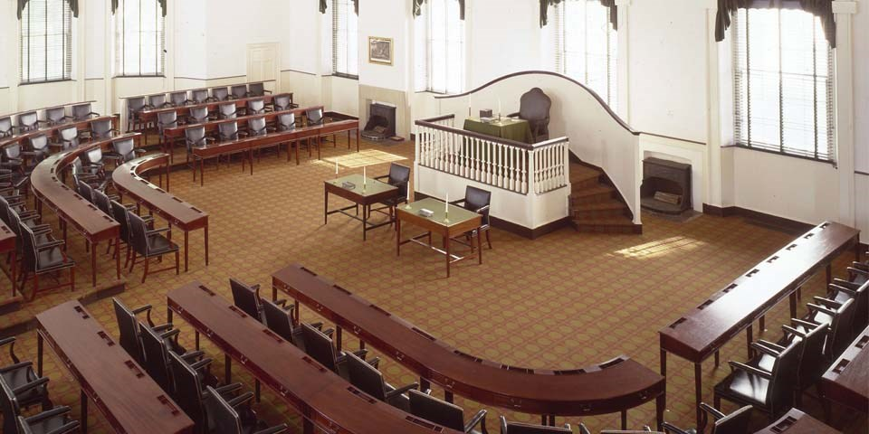 Color photo of the interior of Congress Hall, looking down on the House of Representatives with three rows of desks and chairs in a horseshoe shape facing a raised dais with one large chair.