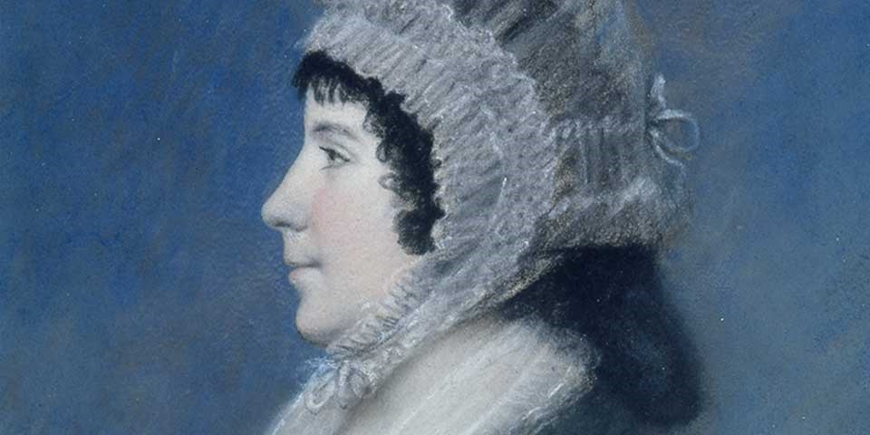 Detail of a pastel portrait of Dolley Madison, a woman shown in profile with dark hair under a white lace bonnet.