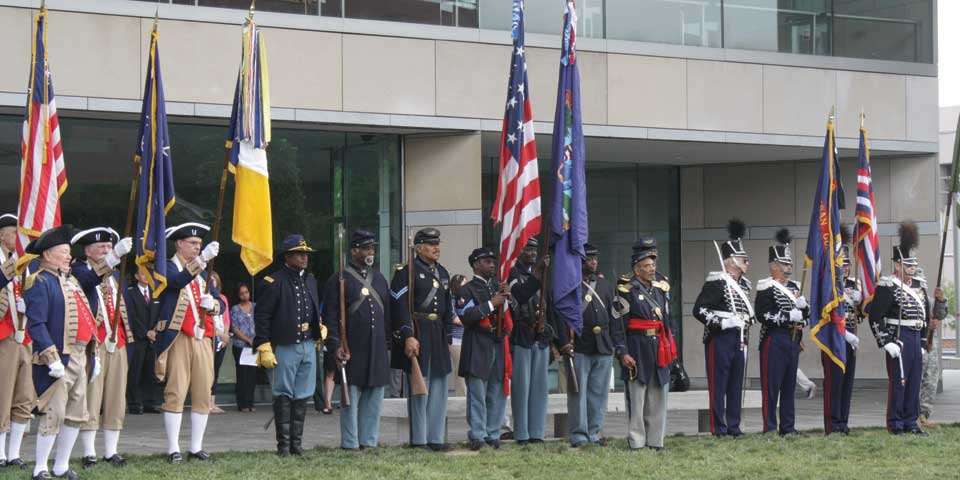 Color photo of reenactors dressed in military uniforms from different periods in history holding flags and standing in a line.