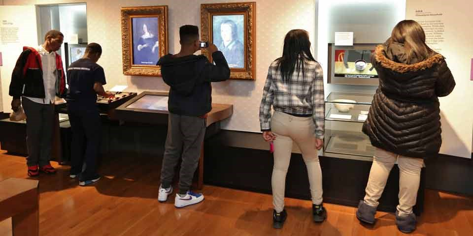 Color photo of five teens with their backs to the camera, looking at the exhibits in the Benjamin Franklin Museum