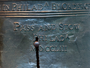 "Color photo showing a detail of the Liberty Bell focusing on a thin crack growing out of a much larger crack in the ""P"" of ""Phila"" on the bell."