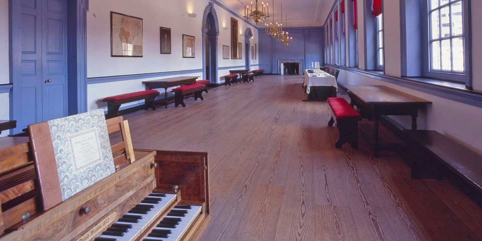 Color photo of a long, wood-floored room with a harpsichord in the foreground and benches lining the walls.