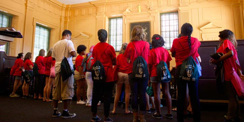 Color photo showing a group of teens in matching red shirts from the back as they look at a room in Independence Hall.