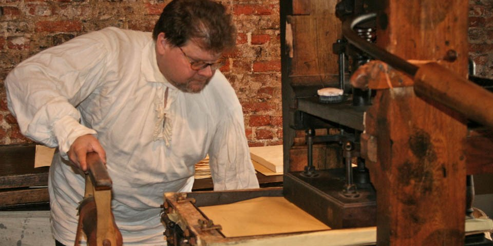 Color photo of man in 18th-century costume demonstrating the printing press.