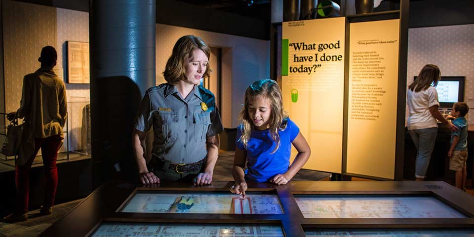 "Color photo of female park ranger looking at a screen on an exhibit table with a young girl; exhibit panel with the words ""What Good Have I Done Today"" is visible behind them."