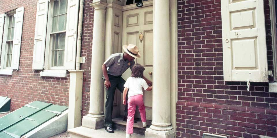 Color photo of a male park ranger and a small child  standing next to each other on a doorstep, working together to turn the doorknob.