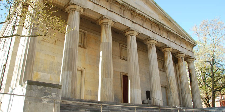 Exterior view of the north facade of the Second Bank of the United States showing eight marble columns topped with a triangular pediment.