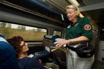 Rails & Trails volunteer talking with Amtrak passengers on the train