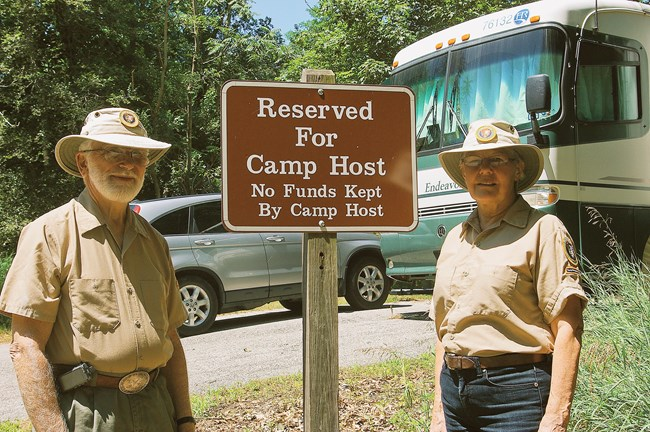 Two campground hosts next to camping sign