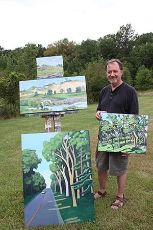 2010 Artist in Residence Victor Pytko standing next to 4 of the 6 paintings completed during his residency.