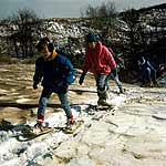 young people actively walking up a snow covered dune on snowshoes