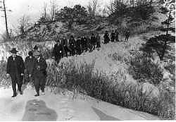 black and white picture from 1916 showing people walking down off a sand dune