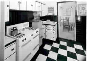 black & white photo of kichen with stove, water cooler, black and white checked tile floor and cabinets.