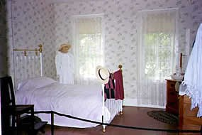 bedroom with brass post bed with 2 large window on the wall beside it