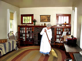 room with rag rug on floor with lady sweeping it, windows and bookcases on wall on both sides of a fireplace.