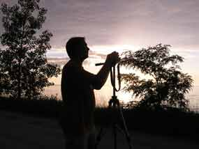 silhouette of man standing behind a tripod with camera on to, trees and sky in background