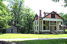 3 story building with large front porch surrounded by grass and trees in the background