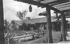 old black and white picture of a log cabin with a landscaped yard